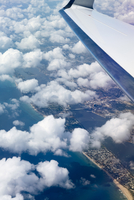 Close-up of aircraft wing flying in cloudy sky over cityscape and sea 11100091077| 写真素材・ストックフォト・画像・イラスト素材|アマナイメージズ