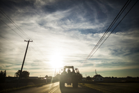 Tractor on road against cloudy sky in town 11100091117| 写真素材・ストックフォト・画像・イラスト素材|アマナイメージズ