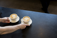 Cropped hands of barista serving frothy drinks on table at cafe 11100091146| 写真素材・ストックフォト・画像・イラスト素材|アマナイメージズ