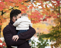 Loving father embracing son while carrying him at park during autumn 11100091149| 写真素材・ストックフォト・画像・イラスト素材|アマナイメージズ