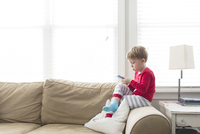 Side view of boy using mobile phone while sitting on sofa at home 11100091200| 写真素材・ストックフォト・画像・イラスト素材|アマナイメージズ