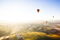 Hot air balloons flying over landscape against clear sky during sunny day 11100091284| 写真素材・ストックフォト・画像・イラスト素材|アマナイメージズ