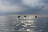 Rear view of female friends surfing in sea against cloudy sky 11100091299| 写真素材・ストックフォト・画像・イラスト素材|アマナイメージズ
