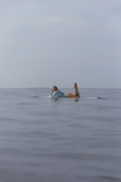 Side view of carefree woman lying on surfboard in sea against sky 11100091306| 写真素材・ストックフォト・画像・イラスト素材|アマナイメージズ