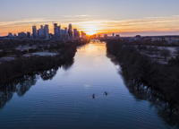 High angle distant view of people sculling on Lady Bird Lake against cityscape during sunrise 11100091335| 写真素材・ストックフォト・画像・イラスト素材|アマナイメージズ