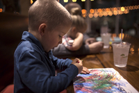 Side view of boy coloring on paper at dining table in restaurant 11100091433| 写真素材・ストックフォト・画像・イラスト素材|アマナイメージズ