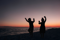 Silhouette siblings dancing at beach against sky during sunset 11100091436| 写真素材・ストックフォト・画像・イラスト素材|アマナイメージズ