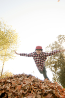 Low angle view of boy falling on autumn leaves against clear sky 11100091591| 写真素材・ストックフォト・画像・イラスト素材|アマナイメージズ