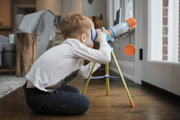 Side view of boy looking through telescope while sitting by door at home 11100091696| 写真素材・ストックフォト・画像・イラスト素材|アマナイメージズ