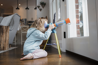 Side view of girl looking through telescope while kneeling by door at home 11100091697| 写真素材・ストックフォト・画像・イラスト素材|アマナイメージズ