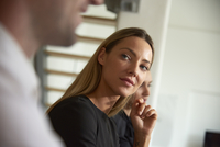 Businesswoman looking at male colleague during business meeting at office 11100091795| 写真素材・ストックフォト・画像・イラスト素材|アマナイメージズ