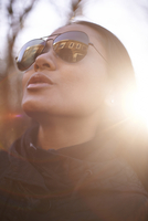 Close-up of confident woman wearing sunglasses during sunny day 11100091799| 写真素材・ストックフォト・画像・イラスト素材|アマナイメージズ