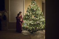 Siblings standing by illuminated Christmas tree at home seen through doorway 11100091818| 写真素材・ストックフォト・画像・イラスト素材|アマナイメージズ
