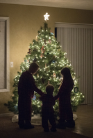 Full length of siblings standing by illuminated Christmas tree at home 11100091819| 写真素材・ストックフォト・画像・イラスト素材|アマナイメージズ