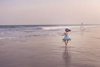 Rear view of happy girl playing at beach against sky during sunset 11100091823| 写真素材・ストックフォト・画像・イラスト素材|アマナイメージズ