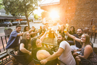 Portrait of happy friends toasting beer while sitting at sidewalk cafe during sunny day 11100091838| 写真素材・ストックフォト・画像・イラスト素材|アマナイメージズ