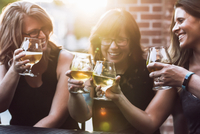 Cheerful female friends toasting beer while sitting at sidewalk cafe during sunny day 11100091839| 写真素材・ストックフォト・画像・イラスト素材|アマナイメージズ