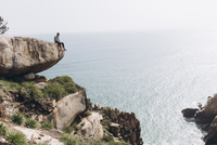 Mid distance view of hiker sitting on cliff while looking at sea 11100091965| 写真素材・ストックフォト・画像・イラスト素材|アマナイメージズ