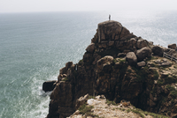 Mid distance view of hiker standing on cliff against sea 11100091968| 写真素材・ストックフォト・画像・イラスト素材|アマナイメージズ