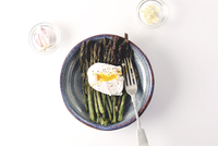 Overhead view of egg with asparagus served in plates by garlic and onions over white background 11100091992| 写真素材・ストックフォト・画像・イラスト素材|アマナイメージズ