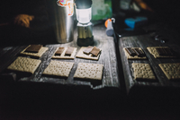 Close-up of crackers and chocolates with illuminated lantern on wooden table at campsite 11100092060| 写真素材・ストックフォト・画像・イラスト素材|アマナイメージズ