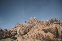 Distant view of boy on rock formations against sky at desert 11100092214| 写真素材・ストックフォト・画像・イラスト素材|アマナイメージズ