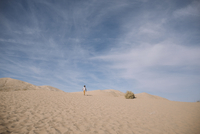 Mid distance view of boy against cloudy sky at desert during sunny day 11100092284| 写真素材・ストックフォト・画像・イラスト素材|アマナイメージズ
