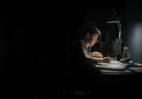 Side view of boy studying at table in darkroom 11100092473| 写真素材・ストックフォト・画像・イラスト素材|アマナイメージズ
