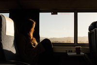 Side view of woman sitting by window in train during sunset 11100092517| 写真素材・ストックフォト・画像・イラスト素材|アマナイメージズ