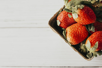 High angle view of strawberries in box on wooden table 11100092567| 写真素材・ストックフォト・画像・イラスト素材|アマナイメージズ