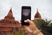 Cropped hand of man photographing Buddhist temple against sky 11100092581| 写真素材・ストックフォト・画像・イラスト素材|アマナイメージズ
