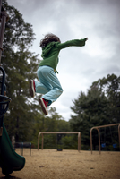 Low angle view of girl jumping on field against cloudy sky at playground 11100092652| 写真素材・ストックフォト・画像・イラスト素材|アマナイメージズ