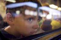 Boy looking through window while traveling in train seen through glass 11100092656| 写真素材・ストックフォト・画像・イラスト素材|アマナイメージズ