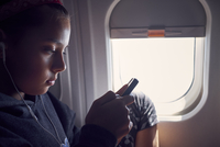 Girl using mobile phone while traveling in airplane 11100092664| 写真素材・ストックフォト・画像・イラスト素材|アマナイメージズ