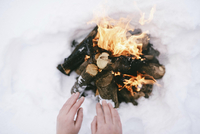 Cropped hands warming over campfire during winter 11100092813| 写真素材・ストックフォト・画像・イラスト素材|アマナイメージズ