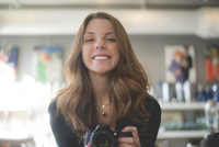 Portrait of happy woman holding camera while standing at home 11100093102| 写真素材・ストックフォト・画像・イラスト素材|アマナイメージズ