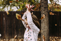 Cheerful girl playing with dry leaves at park during autumn 11100093158| 写真素材・ストックフォト・画像・イラスト素材|アマナイメージズ