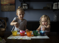 Sisters preparing Easter eggs on table at home 11100093264| 写真素材・ストックフォト・画像・イラスト素材|アマナイメージズ