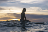 Side view of young woman sitting on surfboard in sea against cloudy sky during sunset 11100093567| 写真素材・ストックフォト・画像・イラスト素材|アマナイメージズ