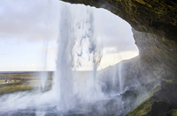 Scenic view of Seljalandsfoss Waterfall against cloudy sky seen through cave 11100093817| 写真素材・ストックフォト・画像・イラスト素材|アマナイメージズ