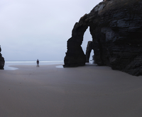 Mid distance view of man standing by rock arch at Cathedral Beach against sky 11100093972| 写真素材・ストックフォト・画像・イラスト素材|アマナイメージズ