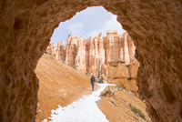 Rear view of hiker walking on mountain during winter seen through cave's entrance at Bryce Canyon National Park 11100093996| 写真素材・ストックフォト・画像・イラスト素材|アマナイメージズ