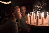 Sister blowing candles on table during Christmas with brother in background at home 11100094038| 写真素材・ストックフォト・画像・イラスト素材|アマナイメージズ