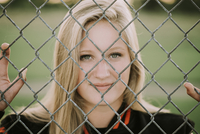 Portrait of softball player standing by fence at playing field