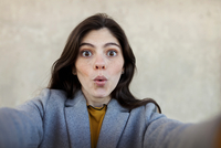 Portrait of surprised young woman making face against wall in city 11100094371| 写真素材・ストックフォト・画像・イラスト素材|アマナイメージズ