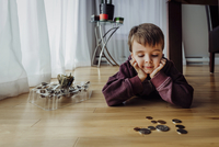 Boy with coins lying on floor at home