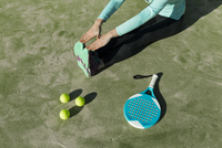Low section of woman stretching with tennis racket and balls on court during sunny day 11100096693| 写真素材・ストックフォト・画像・イラスト素材|アマナイメージズ