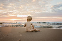 Full length of naked baby boy sitting on sand at beach against cloudy sky during sunset