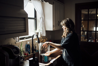 Side view of woman cleaning bowl in kitchen sink at home 11100099155| 写真素材・ストックフォト・画像・イラスト素材|アマナイメージズ