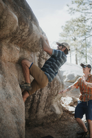 Man assisting friend in climbing rock against sky at forest